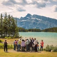 Des touristes visitent le parc national Banff. Ils se tiennent devant le lac Two Jack. Au loin s'élève le mont Rundle.