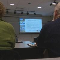 Des gens dans une salle assistent à une présentation sur écran géant