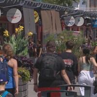 Des touristes devant une rangée de boutiques.
