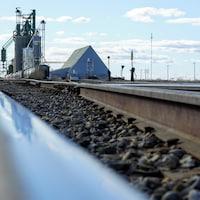 Un chemin de fer devant un silo à grains.