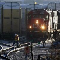 Un travailleur ferroviaire traverse une voie ferrée devant une locomotive du CN dans une gare de triage.