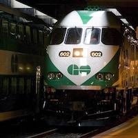 Un train GO entre en gare à Toronto à côté d'un autre train.