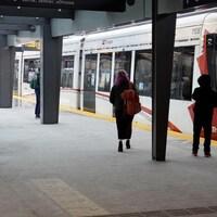 Un train à l'arrêt près de 3 passagers en attente.