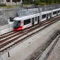 Un train léger file sur les rails à l'extérieur.