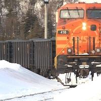 Un train transportant du minerai circule sur le rail enneigé.