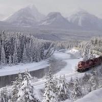 Un train rouge du Canadien Pacifique roule au milieu de sapins recouverts de neige, le long d'une rivière à moitié gelée. Au loin, on voit les sommets enneigés des montagnes Rocheuses.