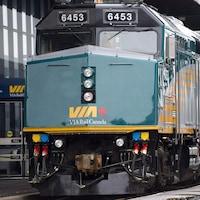 Un employé regarde passer un train de VIA Rail.