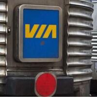 Des vagons d'un train de Via Rail. À gauche, le logo du transporteur, à droite, le mot «Canada» avec un drapeau canadien.