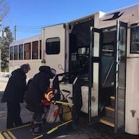 Un usagé du transport adapté embarque dans un autobus.
