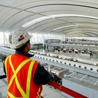 Un employé de la compagnie Aecon dans un aéroport.