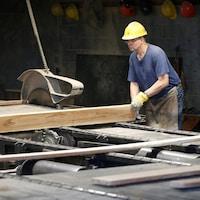 Un travailleur manie une pièce de bois dans un moulin à scie