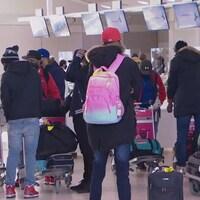 Des dizaines de personnes attendent devant les bureaux d'enregistrement de l'Aéroport Pearson de Toronto avec leurs valises en main et un masque sur le visage.