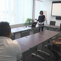 Trois hommes sont assis dans une salle de réunion. Ils regardent une femme debout qui fait une présentation.
