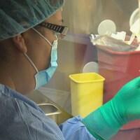 Une infirmière injecte un médicament au soluté.