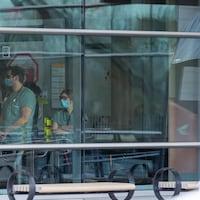 Des travailleurs de la santé, portant un masque, vus à travers une fenêtre de l'urgence du CHAUR de Trois-Rivières.