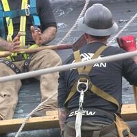 Des travailleurs sur un toit, retenus par des harnais de sécurité.