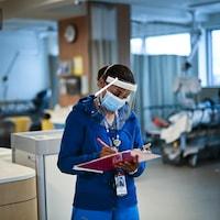 Une infirmière prend des notes.