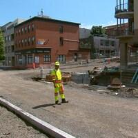 Un travailleur au centre d'un grand chantier de construction sur une rue, avec des commerces et restaurants autour