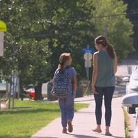 Une mère et sa fille marchent dans une zone scolaire.
