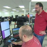 Trent Oster est debout derrière un homme qui joue à un jeu vidéo assis à un bureau.