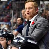 Trevor Letowski est debout derrière des joueurs de hockey sur le côté de la patinoire.