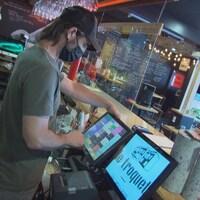 Un serveur prend la commande d'un client dans un bar.