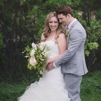 Troy et Carissa Gasper le jour de leur mariage.  Elle tient des fleurs dans la main pendant que son mari la tient dans ses bras.