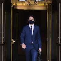 M. Trudeau, masqué, sortant d'un immeuble.