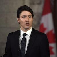 Justin Trudeau devant un drapeau du Canada.