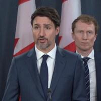 Justin Trudeau au micro, Marc Miller en arrière-plan.