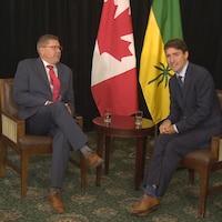 Scott Moe et Justin Trudeau assis dans des chaises devant les drapeaux de la Saskatchewan et du Canada. Scott Moe regarde Justin Trudeau avec un air grave. Justin Trudeau parle au public en souriant.