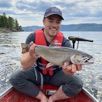 Le pêcheur heureux tient la truite dans ses mains.
