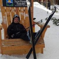 Truman Tremblay porte des skis et est aussi dans une chaise démesurée.
