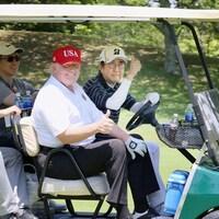 Deux hommes assis dans une voiturette de golf brandissent leur pouce en signe de bonne entente sur un terrain de golf.