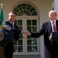 Tout sourire, Jair Bolsonaro et Donald Trump se serrent la main devant la Maison-Blanche.
