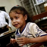 Une fillette tient un comprimé et un verre d'eau.