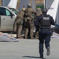 Un policier en noir se rue vers un groupe de policiers en vêtements militaires attroupés.
