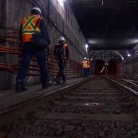 Des hommes vêtus de vestes réfléchissantes s'engouffrent dans le tunnel.