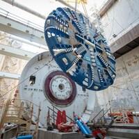 On voit en contre-plongée une roue géante, munie de lames coupantes, qui est suspendue à des câbles. Derrière se trouve le bouclier du tunnelier, qui recevra cette roue. Le tout se trouve au centre d'un grand puits rectangulaire aux parois bétonnées.