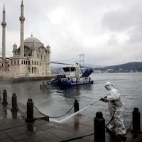 Un employé revêtu des pieds à la tête d'une camisole de protection vaporise du désinfectant sur le pavé, au bord de l'eau, avec une mosquée en fond de décor.