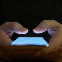 Un homme tenant entre ses mains un cellulaire allumé.
