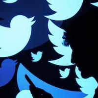 Une silhouette regarde un téléphone. Il y a plusieurs logos de Twitter en arrière-plan.