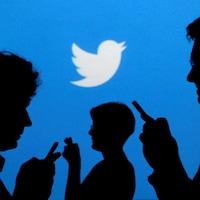 Des silhouettes de personnes tenant un téléphone dans leurs mains devant un mur bleu sur lequel est dessiné le logo de Twitter.