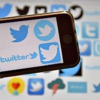 Des logos de Twitter sont visibles sur un téléphone cellulaire et sur un écran en arrière-plan.