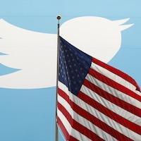 Le logo du réseau social twitter est placé derrière un drapeau des États-Unis.