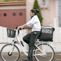 Une femme sur un vélo portant un pantalon DELIVEROO, avec un sac de livraison UBER EATS à l'arrière.