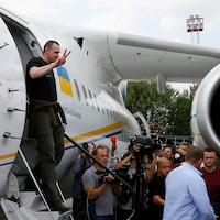 OlegSentsov fait un signe de la victoire avec sa main droite alors qu'il descend les escaliers de l'avion devant une foule et des caméras.