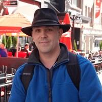 Ulrique porte un chapeau noir et sourit, debout devant une terrasse.