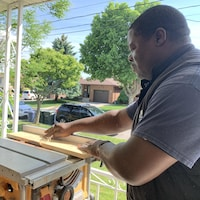 Un homme travaille sur un morceau de bois