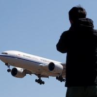 Un homme regarde un avion atterrir.